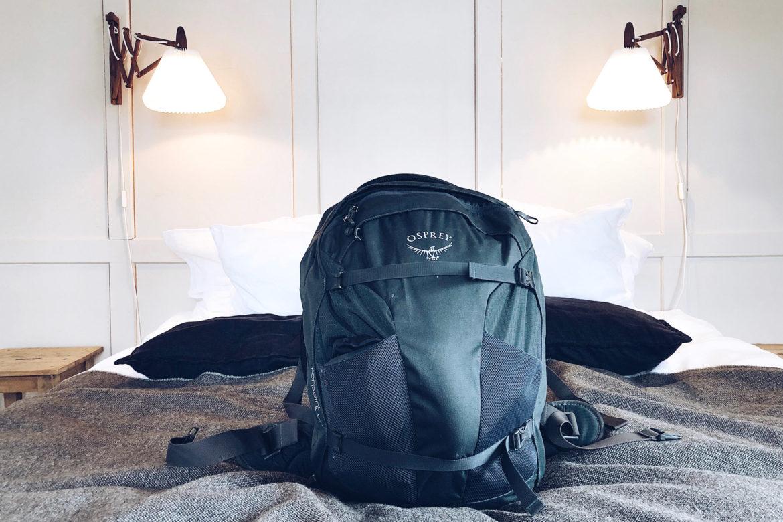Handgepäck Osprey Rucksack liegend auf einem Hotelbett.